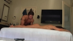 Massuer is stimulating honey's cunt with vibrator after rub down